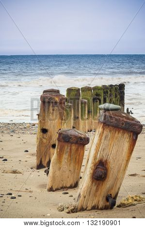 Weathered and rusted sea defenses on a beach