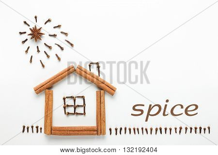 Concept cooking. The idea of a figure made of spices. House, sun and grass made of cinnamon sticks, cloves and star anise isolated on white background