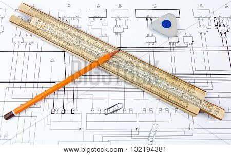 Professional scale ruler, pencil, eraser and some staples on the blueprint