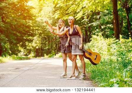 Two woman hitchhike along the road through woods
