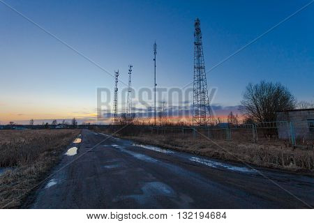 Communications towers with antennas and equipment   are located near the road at the sunset
