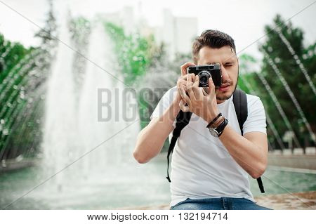 Outdoor summer lifestyle portrait of a handsome man having fun in city with camera. Travel photo of photographer. Young man taking photo.