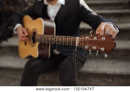 Young hipster playing guitar.  Close up of a man tuning his guitar.