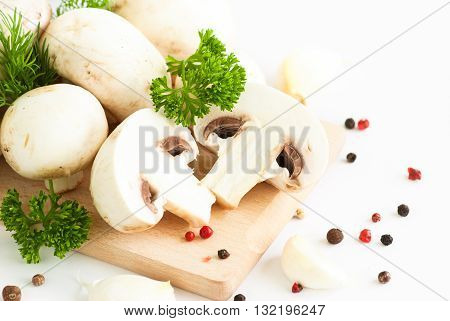 Champignon. White mushrooms on white background with herbs.