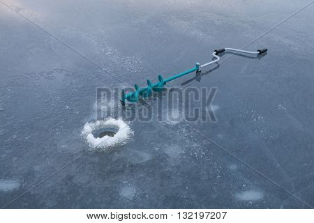 The Ice Fishing Drill on the Lake and the ice hole