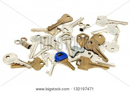 A variety of old gold and silver colored keys on a white background.