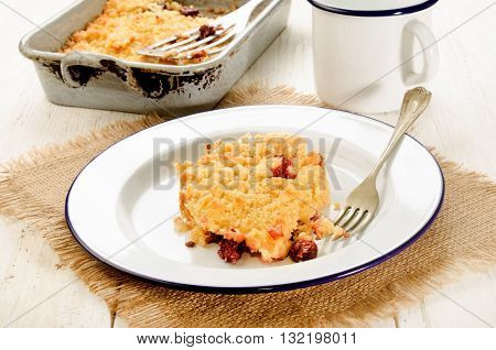 home made cherry crumble on enamel plate with fork mug and baking tin
