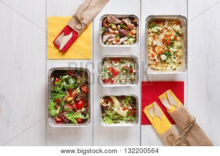 Eating right concept, healthy food. Weight loss diet, clean food take away in aluminium boxes with cutlery, vegetable salads and meat top view, flat lay at white wood background. Fitness food.