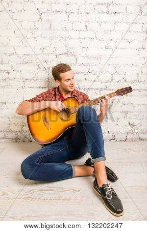 Handsome Man  Siting On Floor And Playing On The Guitar