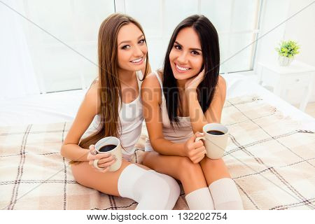Pretty Sexy Gossip Girls Drinking Coffee And Sitting On The Bed
