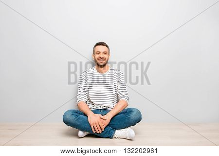 Cheerful Happy Man Sitting On Floor With Crossed Legs