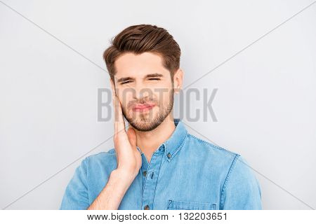 Depressed Ill Man Having Toothache And Touching Cheek