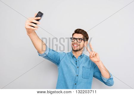 Happy Man In Glasses Making Selfie On Smartphone And Showing Two Fingers
