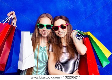 Portrait Of Two Happy Shoppers In Glasses With Packages