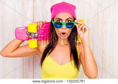 Portrait Of Shocked Woman In Pink Hat And Glasses Holding Skateboard