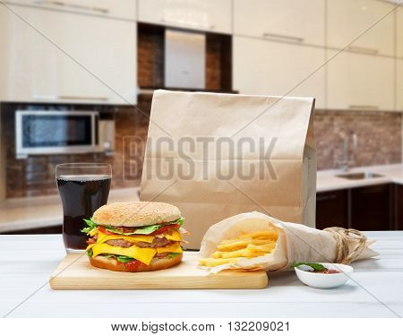 Fast food. Brown wrapping paper package with copyspace. Hamburger, potato fries, drink at kitchen. Takeaway food. French fries, packaging, Cola glass, big cheese hamburger at wood.
