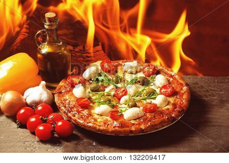 Delicious pizza and fresh vegetables on wooden table against fire flame background