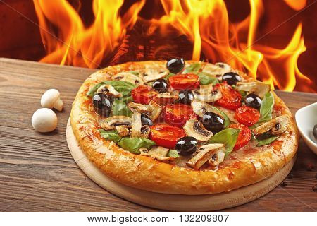 Delicious hot pizza on wooden table against fire flame background