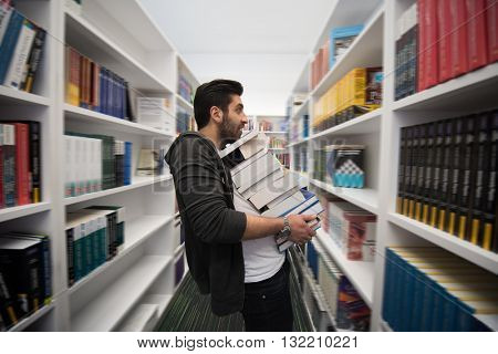 Student holding lot of books in school library. Hard worker and persistence concept.