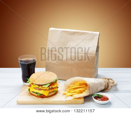 Fast food. Brown wrapping paper package with copyspace. Hamburger, potato fries, cola drink. Takeaway food. Wrapped French fries, packaging, Cola glass, tomato sauce, double cheeseburger at wood.