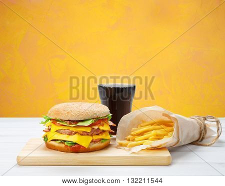 Fast food with copyspace. Hamburger, potato fries at brown wrapping paper, cola drink. Takeaway food. French fries, Cola glass, double cheese hamburger at white wood and yellow background.