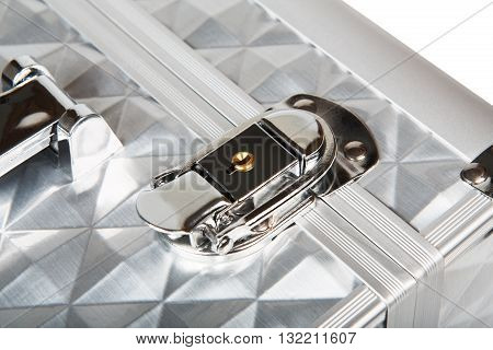 Professional aluminum makeup box lock closeup isolated at white background. Make up case for professional make-up artist. Beautician tools silver metal suticase.
