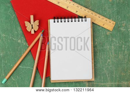 Office set with notebooks, colored pencils and ruler on green wooden background