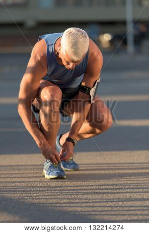 Man tying running shoes laces  before jogging workout