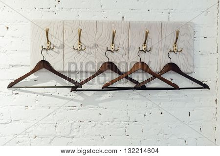 Wood coat hanger on a white brick wall