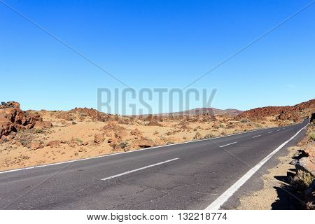 highway through desert landscape with clear blue sky