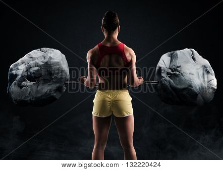 Muscular woman raises two big boulders with a barbell
