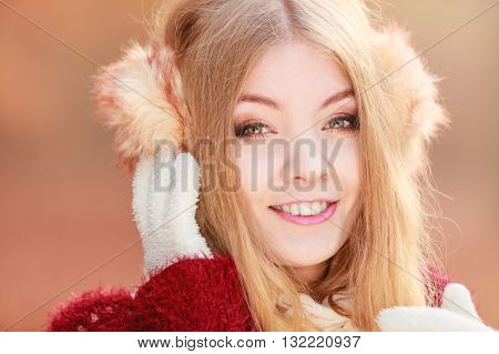 Portrait of pretty attractive fashionable woman in fall forest park. Gorgeous young girl in earmuffs. Autumn winter fashion.
