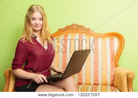 Young fashionable woman girl sitting on vintage retro sofa couch using laptop computer surfing the internet. Fashion and modern technology.