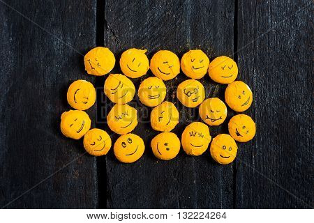 Some yelow pebble smile on black wood table. Emoticon fun and happy. Smile is a handdraw. Flat lay.