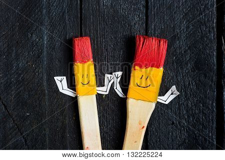 Two art brushes with smiley face . White are clipped. Two brushes with ink smile like a toy with hands.