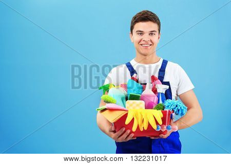 Man holding plastic bucket with brushes, gloves and detergents on grey background