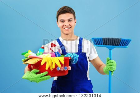 Man holding plastic basin with brushes, gloves and detergents on blue background