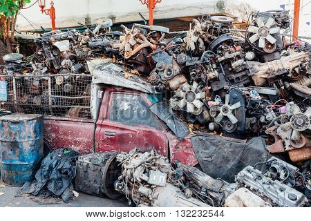 Pickup truck buried under a lot of car engines on the street of Bangkok