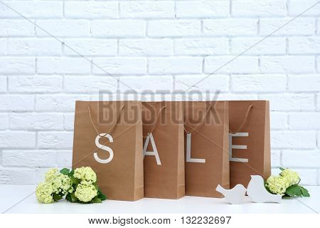Recycled paper shopping bags on brick wall background