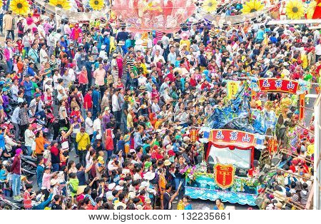 Binh Duong, Vietnam - February 22nd, 2016: Chinese Lantern Festival with truck models fruits mountain parade on streets crowded cheering people really busy roadside morning in Binh Duong, Vietnam