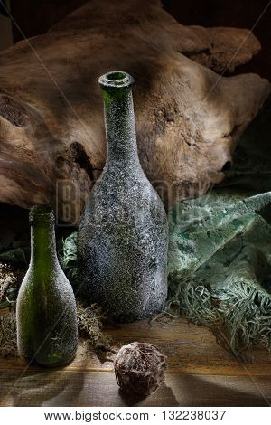 Two green botles coated with frost and old wood