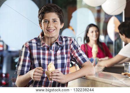 Smiling Boy Having Ice Cream At Parlor
