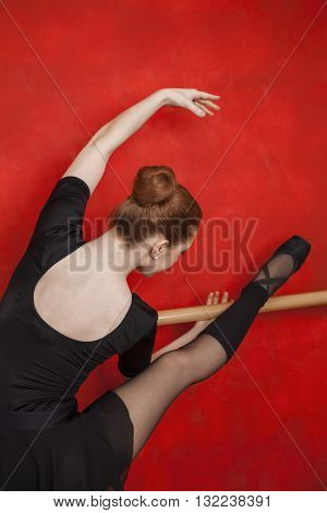 Ballerina Stretching At Barre Against Red Wall