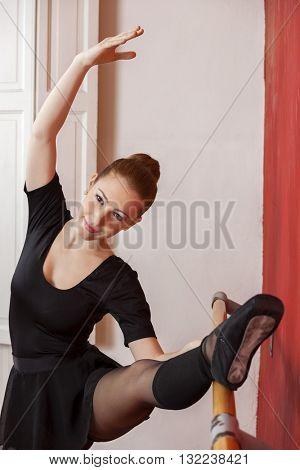 Beautiful Ballerina Practicing At Barre In Studio