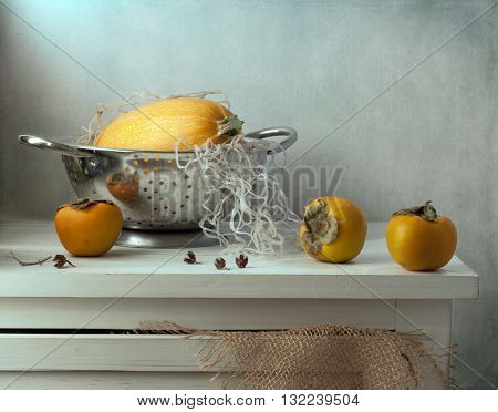 Still life with pumpkin and persimmon on wooden vintage table