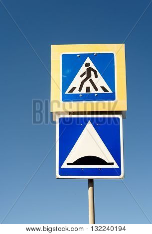 Road saefty sign of a pedestrian crossing with a speed humo warning symbol