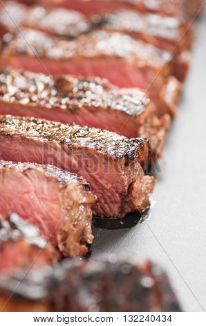 thick ribeye steak seared rare on a cast iron grill