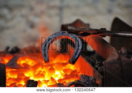 Blacksmith forges a horseshoe in a smithy