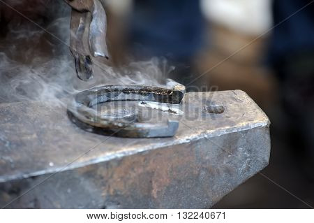 Blacksmith forges a horseshoe for horse close-up