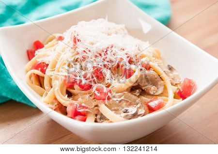 creamy alfredo fettucini pasta with crimini mushrooms and fresh tomatoes topped with parmesan